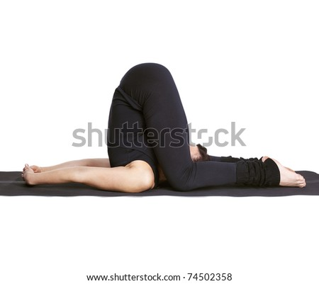 full-length portrait of beautiful woman working out yoga excercises karnapidasana pose on fitness mat - stock photo