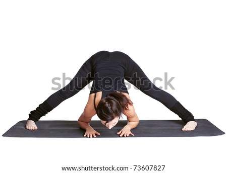 full-length portrait of beautiful woman working out yoga excercises prasarita padottanasana on fitness mat - stock photo