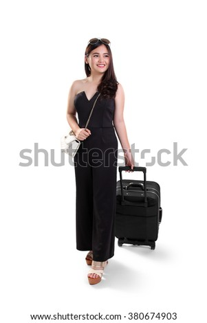 Full length portrait of beautiful young Asian woman smiling while traveling with suitcase, isolated on white background - stock photo