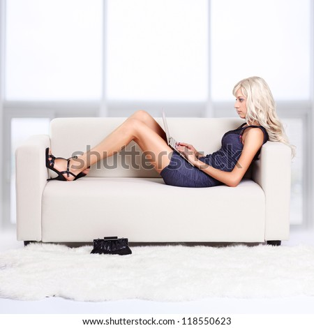 full-length portrait of beautiful young blond woman relaxing on couch with laptop - stock photo