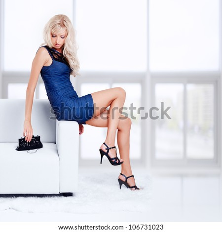 full-length portrait of beautiful young blond woman with handbag sitting on couch with white furs on floor - stock photo
