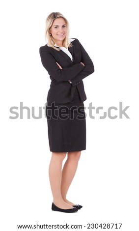 Full length portrait of beautiful young businesswoman standing arms crossed over white background - stock photo