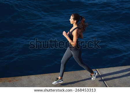 Full length portrait of beautiful young woman running along the cement pier with amazing big ocean waves on background - stock photo