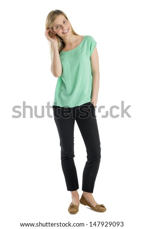 Full length portrait of beautiful young woman smiling with hand in pocket standing against white background - stock photo