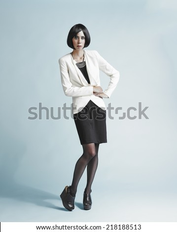 Full length portrait of beautiful young woman wearing a white jacket and skirt - studio shot - stock photo