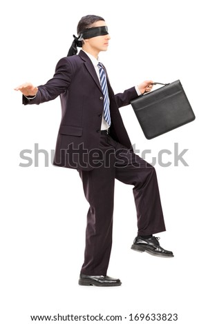 Full length portrait of blindfolded young businessman with briefcase walking, isolated on white background - stock photo