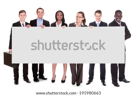 Full length portrait of business team holding blank placard against white background - stock photo