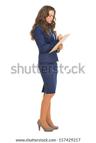 Full length portrait of business woman writing something in clipboard - stock photo