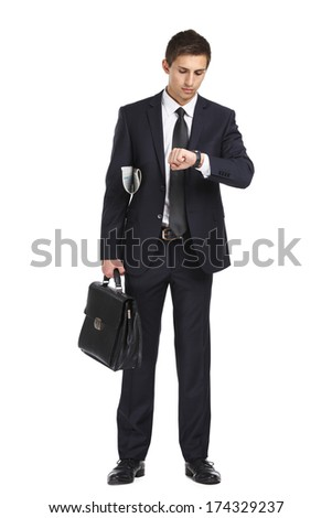 Full-length portrait of businessman handing briefcase and looking at his watch, isolated on white. Concept of business and success - stock photo