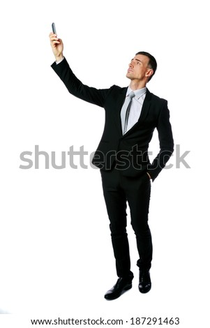 Full-length portrait of businessman searching connection on the phone over white background - stock photo