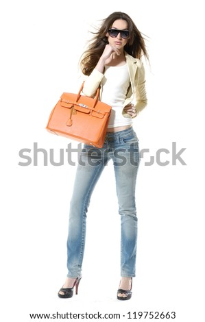 full-length portrait of casual fashion woman holding bag posing in studio - stock photo