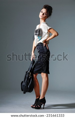 full-length portrait of casual fashion woman with bag posing in studio  - stock photo