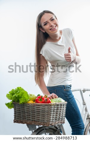 Full length portrait of cheerful girl riding with admiration the bicycle with basket of healthy food.  She is smiling and gesturing, isolated on a white background - stock photo