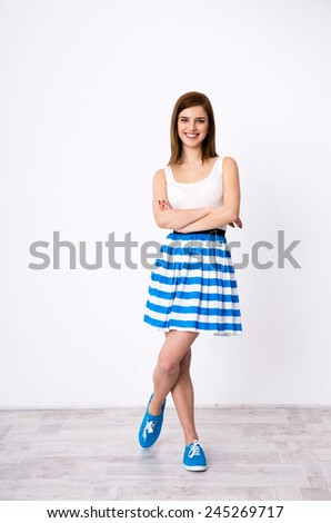 Full length portrait of cheerful woman standing with arms folded - stock photo