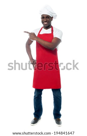 Full length portrait of chef in uniform pointing away - stock photo