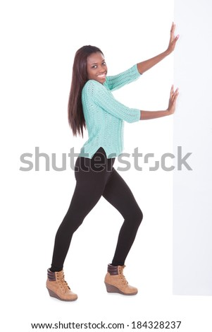 Full length portrait of confident African American woman pushing billboard against white background - stock photo