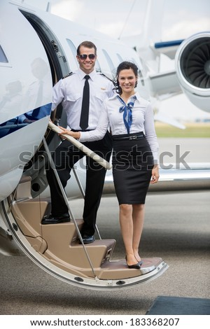 Full length portrait of confident airhostess and pilot standing on ladder of private jet at airport terminal - stock photo