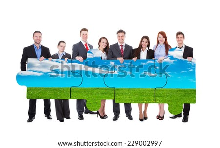 Full length portrait of confident business people joining nature jigsaw pieces against white background - stock photo