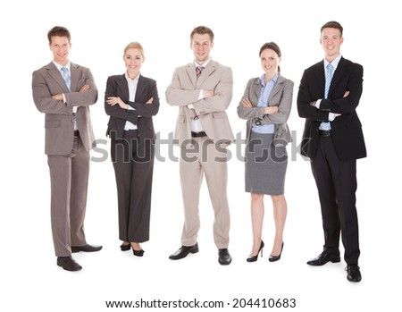 Full length portrait of confident business team standing arms crossed against white background - stock photo