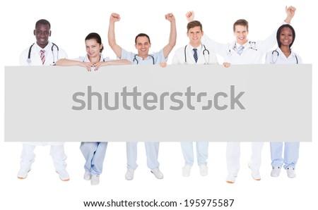 Full length portrait of confident doctors holding blank billboard over white background - stock photo