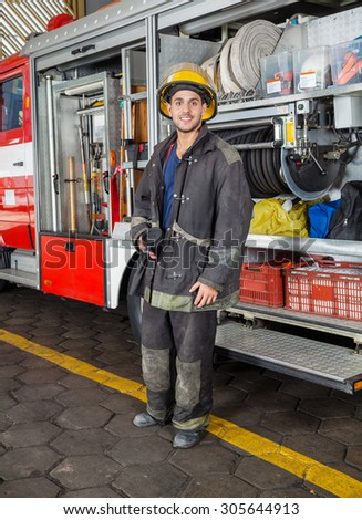 Full length portrait of confident fireman holding coffee mug while standing by truck at fire station - stock photo
