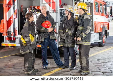 Full length portrait of confident male firefighter standing with team against truck at fire station - stock photo