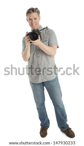 Full length portrait of confident male photographer with camera and umbrella lights standing over white background - stock photo