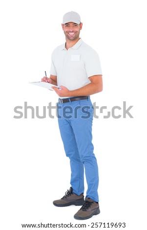 Full length portrait of confident male supervisor writing on clipboard over white background - stock photo