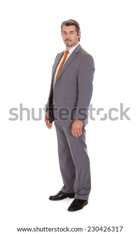 Full length portrait of confident mature businessman standing over white background - stock photo