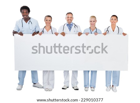Full length portrait of confident medical team holding blank billboard over white background - stock photo