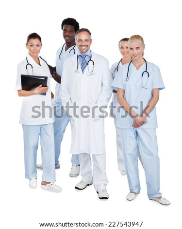 Full length portrait of confident multiethnic medical team standing over white background - stock photo