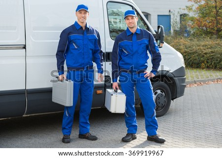 Full length portrait of confident technicians standing against truck on street - stock photo