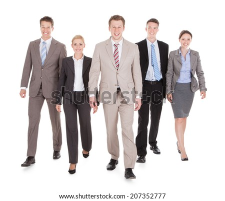 Full length portrait of confident young business people walking isolated over white background - stock photo