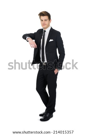 Full length portrait of confident young businessman leaning on invisible wall over white background - stock photo