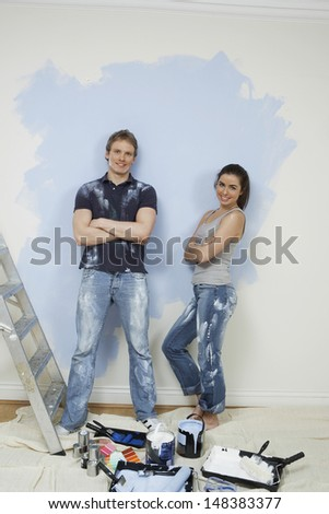 Full length portrait of confident young couple standing against wall with painting tools in foreground - stock photo