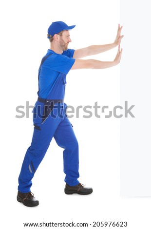 Full length portrait of confident young male cleaner holding mop standing isolated over white background - stock photo