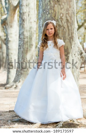 Full length portrait of cute girl in white dress in forest. - stock photo