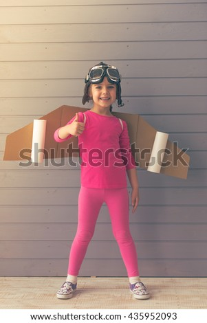 Full length portrait of cute little girl dressed like a pilot with toy wings showing Ok sign, smiling and looking at camera, against gray wall - stock photo