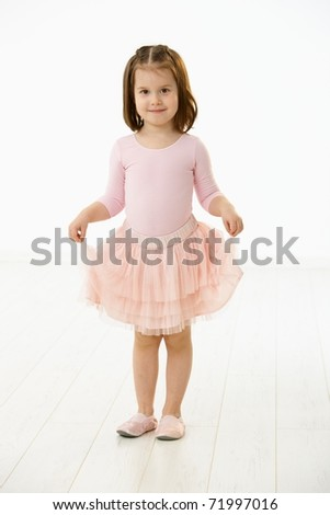 Full length portrait of cute little girl (4-5 years) wearing ballet costume looking at camera, smiling. Studio shot over white background.? - stock photo