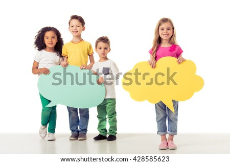 Full length portrait of cute little kids in casual clothes holding speech bubbles, looking at camera and smiling, isolated on a white background - stock photo