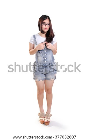 Full length portrait of cute shy nerdy girl standing awkwardly, isolated on white background - stock photo