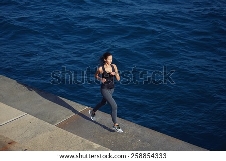 Full length portrait of cute young woman out jogging along the coastline at sunny day, dynamic picture with sport girl in action running over ocean waves background - stock photo
