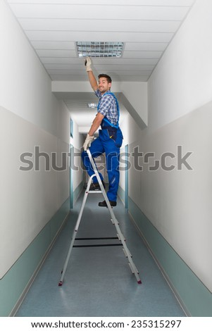 Full length portrait of electrician on stepladder installs lighting to the ceiling in office - stock photo
