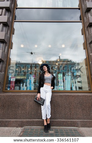 Full length portrait of elegant and trendy woman having a rest after strolling in the city center, young female model dressed in stylish clothes posing on the background on store in the urban setting - stock photo