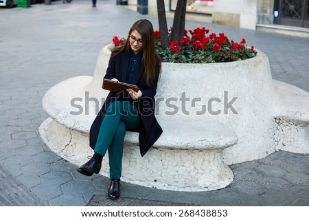 Full length portrait of elegant business woman in glasses working with digital tablet pc outdoors - stock photo