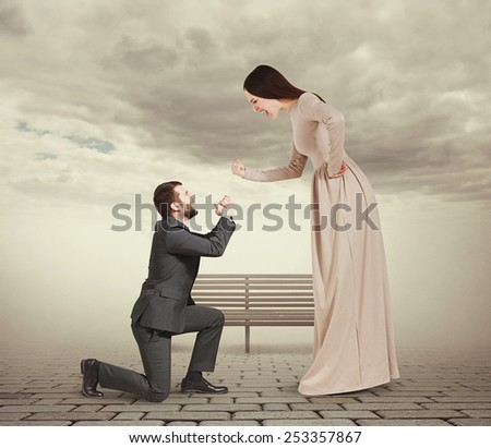full length portrait of emotional couple in foggy park. woman screaming and showing fist, man standing on knee and apologizing - stock photo