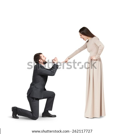 full length portrait of emotional couple over grey background. angry woman pointing and screaming at man, man standing on knee and apologizing. isolated on white background - stock photo