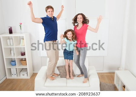Full length portrait of excited family with arms raised jumping on sofa at home - stock photo