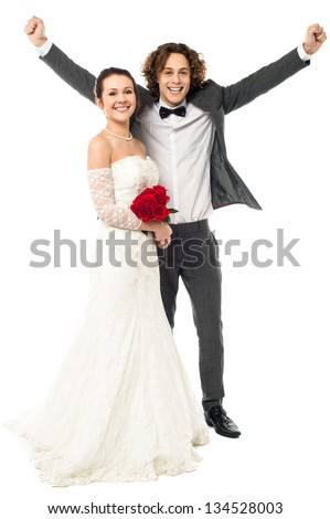 Full length portrait of excited groom posing beside his beloved wife. - stock photo