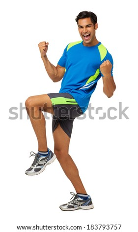 Full length portrait of excited young man in sports clothing celebrating success over white background. Vertical shot. - stock photo